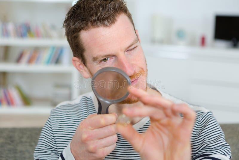 Jeune homme regardant par la loupe photo stock