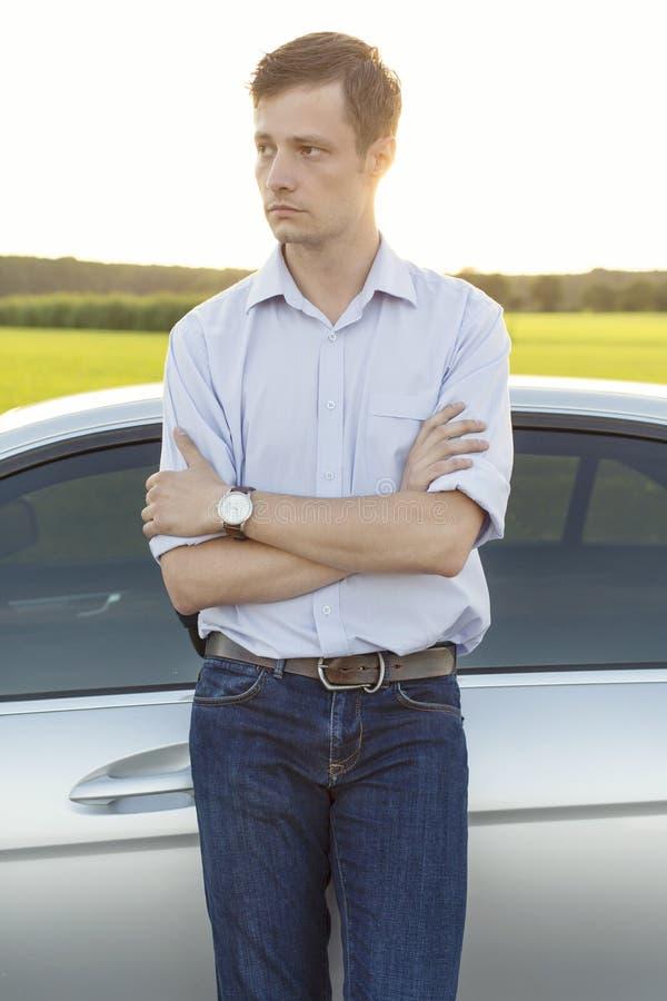 Jeune homme regardant parti tout en se tenant prêt la voiture la campagne photographie stock libre de droits