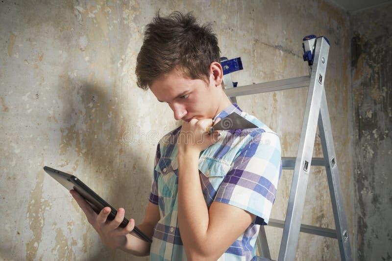 Jeune homme regardant sur les données Internet au sujet des réparations de pièce images stock