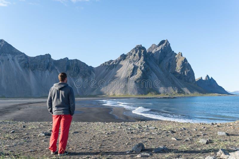 Jeune homme regardant une plage scénique en Islande images stock