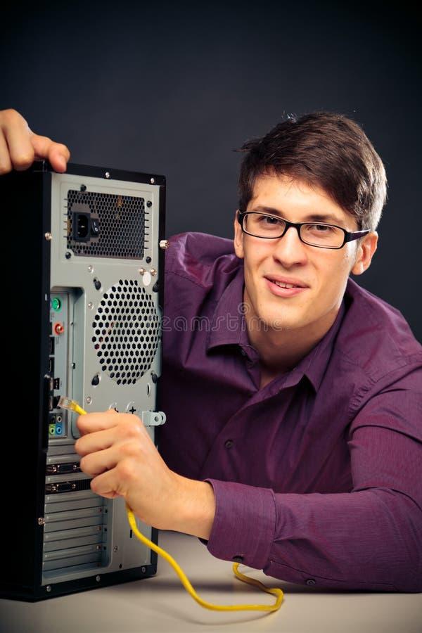 Jeune homme reliant un câble de réseau photo stock