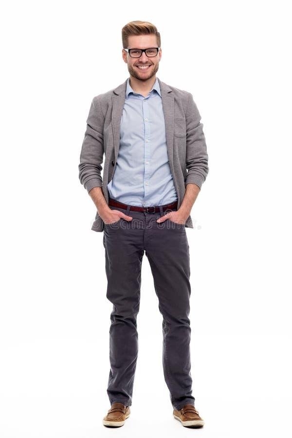 jeune homme restant avec ses mains dans des poches photo stock