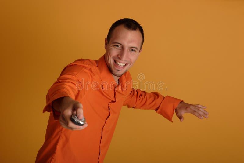 Jeune homme retenant un à télécommande photographie stock libre de droits