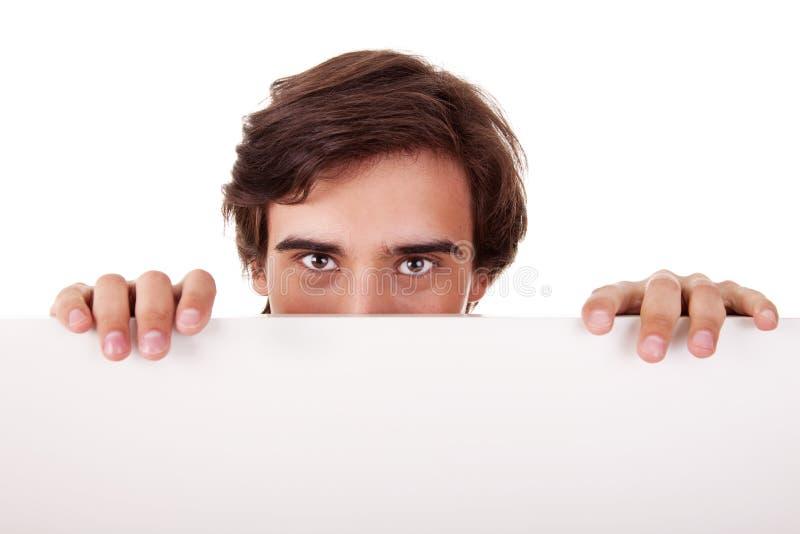 Jeune homme retenant un panneau blanc, regardant à l'appareil-photo image stock