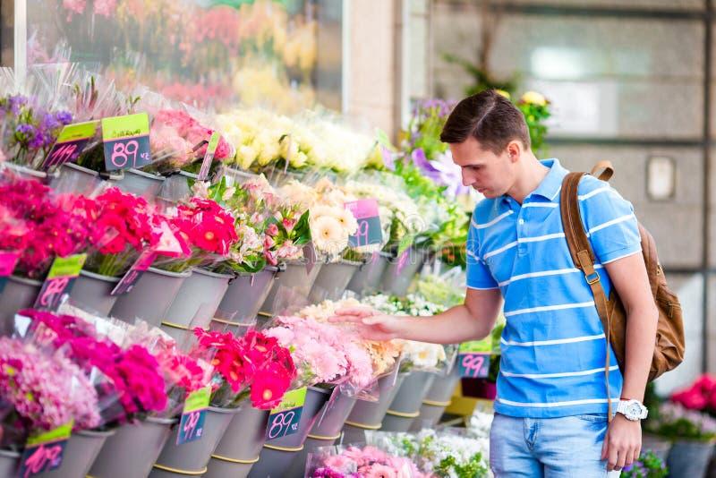 Jeune homme sélectionnant les fleurs fraîches à sa belle amie au marché européen photographie stock