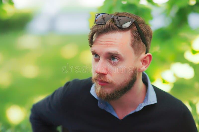 Jeune homme sérieux avec des lunettes de soleil au café de rue photos libres de droits