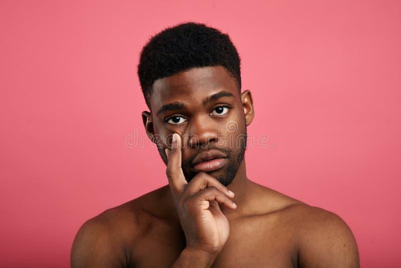 Jeune homme sérieux ayant concentré l'expression réfléchie images stock