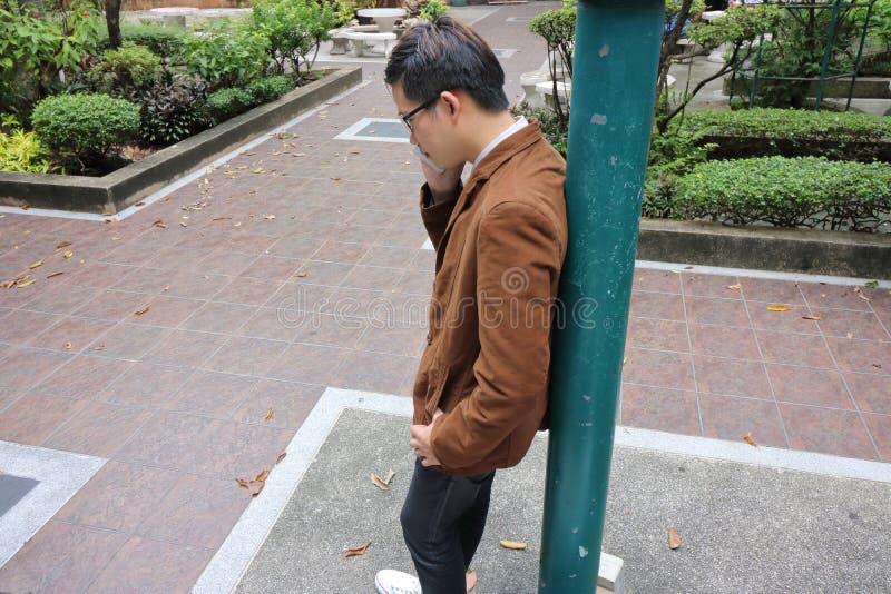 Jeune homme sérieux d'affaires dans le costume parlant au téléphone portable tout en se penchant un poteau au parc extérieur image stock