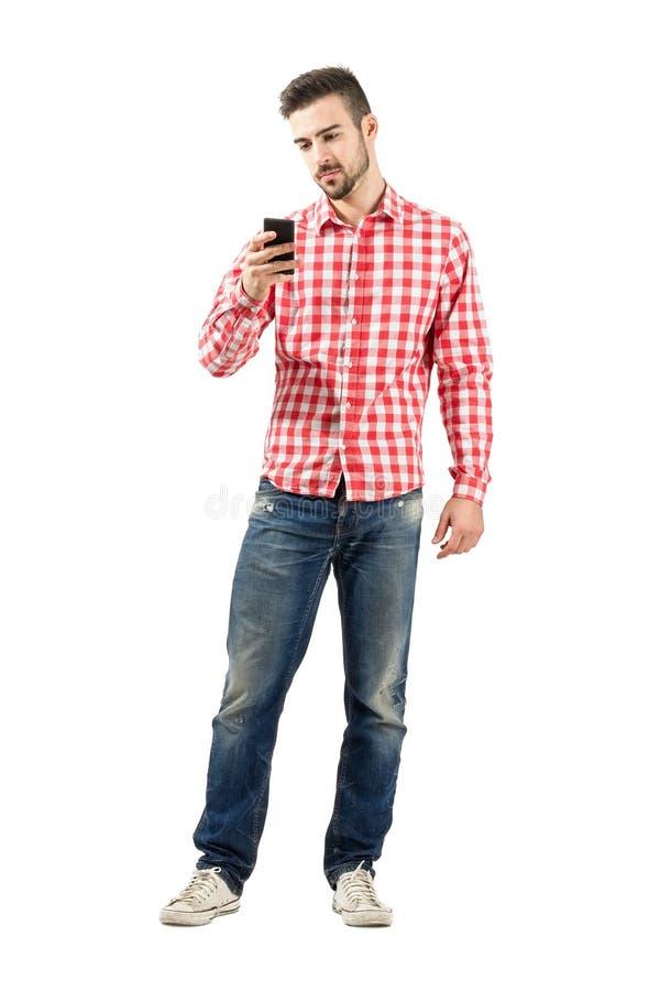 Jeune homme sérieux prenant la photo avec le smartphone images stock