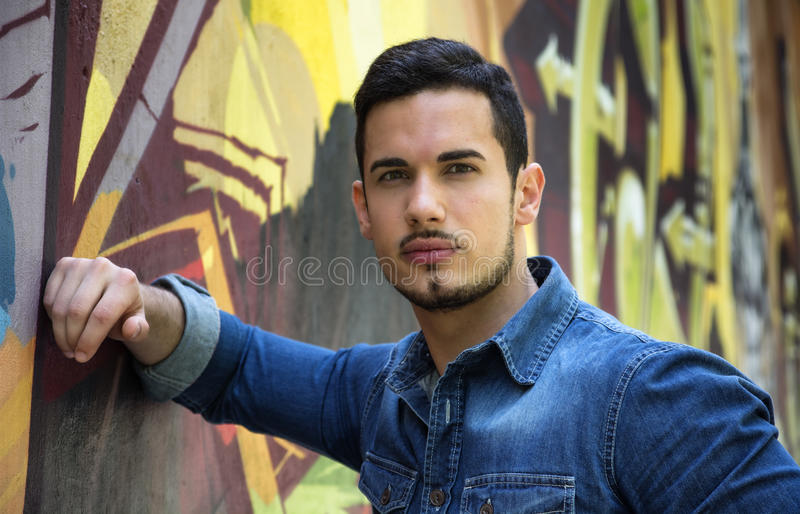 Jeune homme sérieux se penchant sur le mur coloré de graffiti photo stock