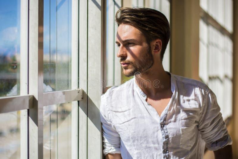 Jeune homme sérieux tenant le bâtiment moderne intérieur photos libres de droits