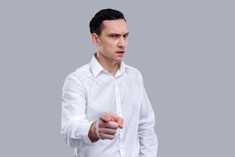 Jeune homme sévère regardant strictement photo stock