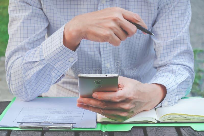 Jeune homme sûr dans la tenue de détente futée tenant le téléphone et le stylo futés avec le regarder tout en se reposant à son f image stock