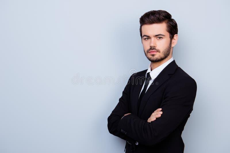 Jeune homme sûr dans le costume noir avec les mains croisées tenant l'ha photos stock