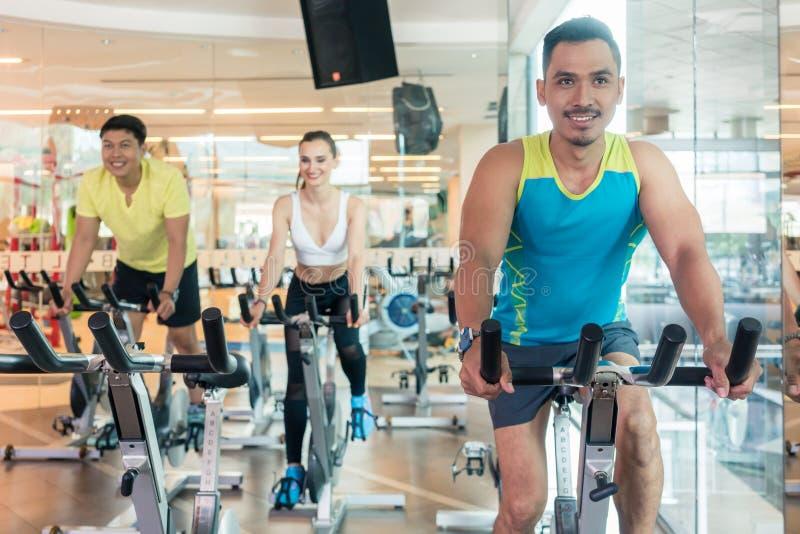 Jeune homme sûr souriant pendant la classe de recyclage d'intérieur dans un centre de fitness moderne photo libre de droits