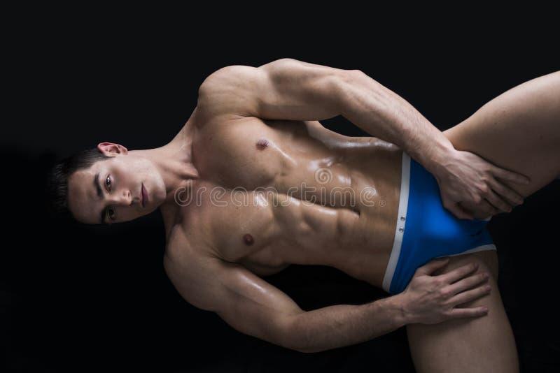 Jeune homme s'étendant sur le plancher avec le corps musculaire nu photographie stock libre de droits