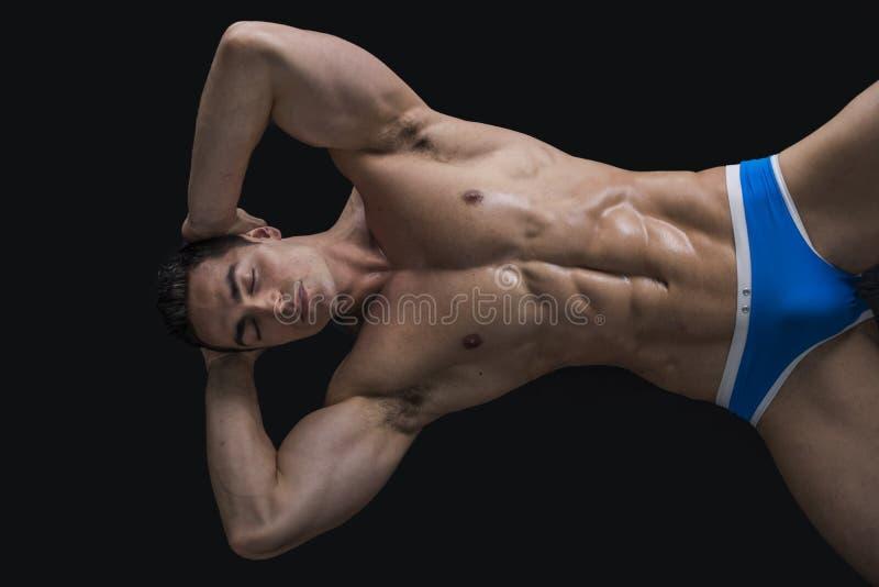 Jeune homme s'étendant sur le plancher avec le corps musculaire nu images stock