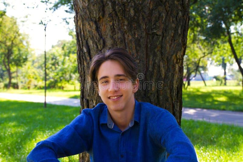 Jeune homme s'asseyant à l'herbe près de l'arbre au parc, regardant la caméra photo libre de droits