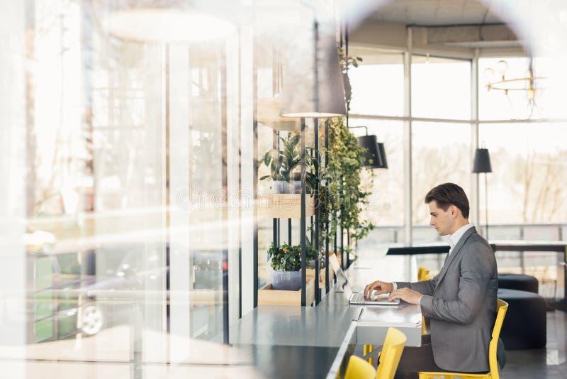 Jeune homme sasseyant au bureau travaillant à la pièce moderne de
