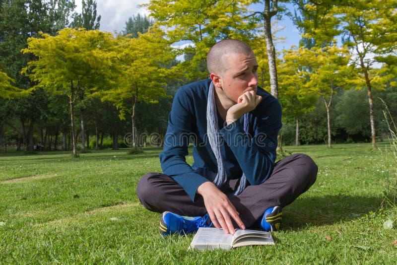 Download Jeune Homme S'asseyant Avec Le Livre En Parc Image stock - Image du concentration, homme: 56485129