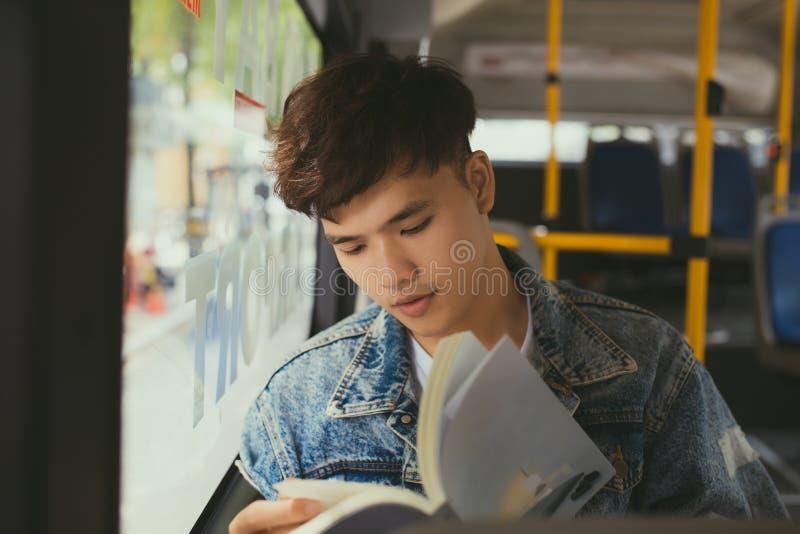 Jeune homme s'asseyant dans l'autobus de ville et lisant un livre photos stock