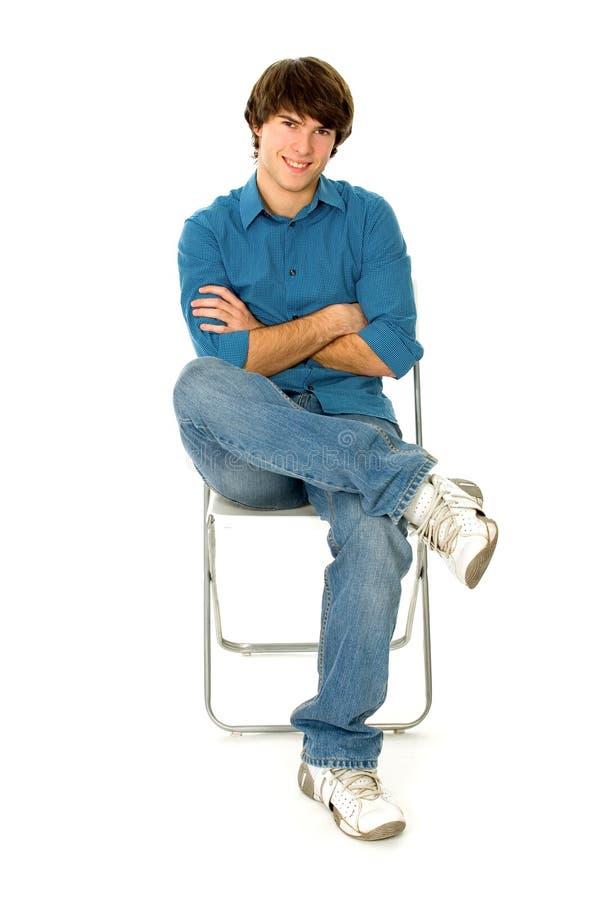 Jeune homme s'asseyant dans la présidence photos stock
