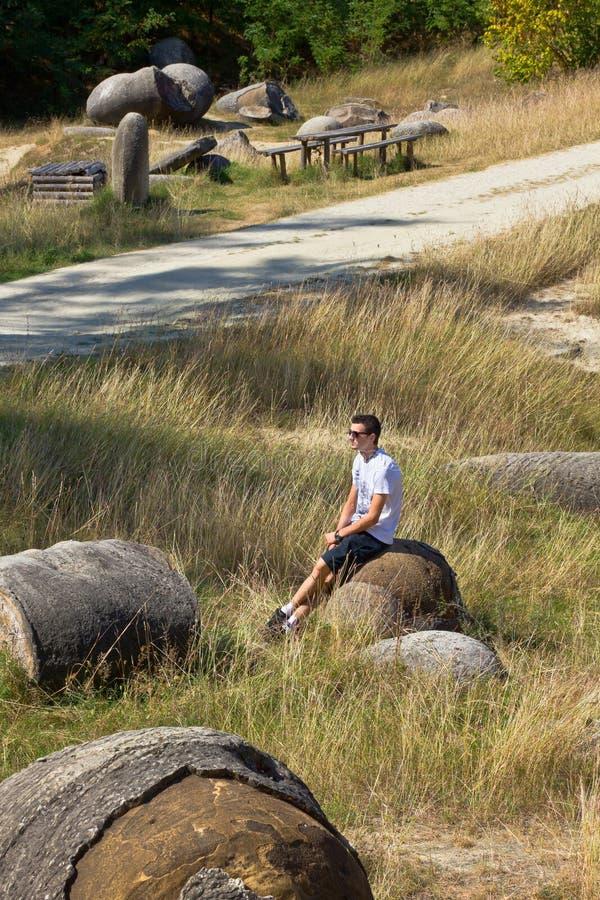 Jeune homme s'asseyant dans le jardin en pierre photo stock