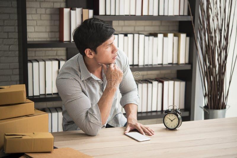 Jeune homme s'asseyant dans un siège social avec la pensée PME, propriétaire images stock