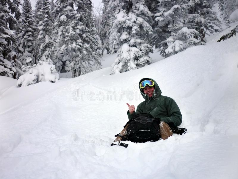 Jeune homme s'asseyant de la neige de poudre photographie stock