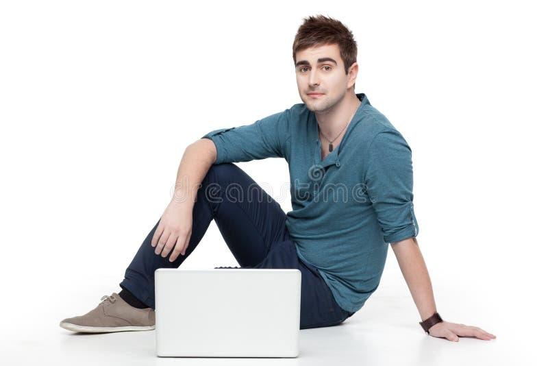 Jeune homme s'asseyant derrière l'ordinateur portatif photographie stock