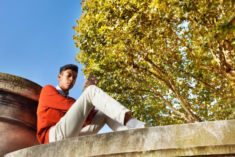 Jeune homme s'asseyant en parc et à l'aide du téléphone intelligent photos stock