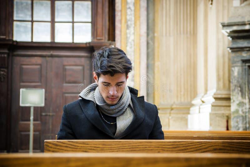 Jeune homme s'asseyant et prière d'agenouillement dans l'église image stock