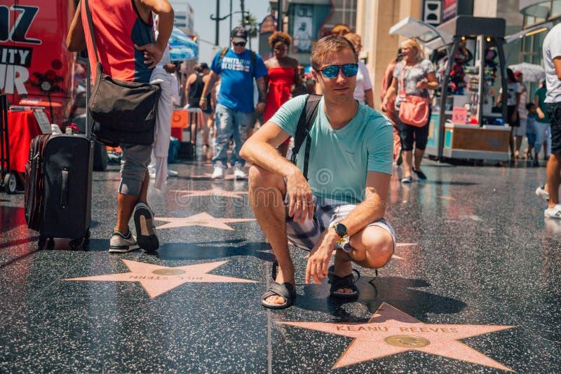 Jeune homme s'asseyant par l'étoile de Keanu Reeves photos stock