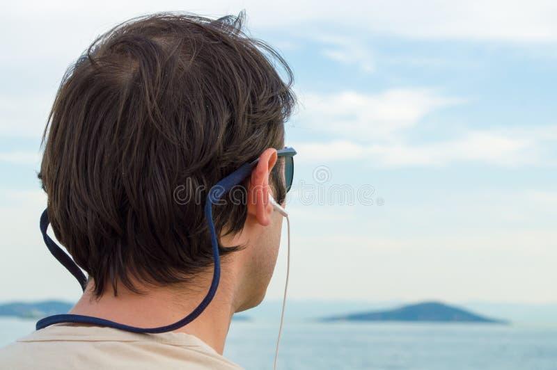 Jeune homme s'asseyant par la mer images libres de droits