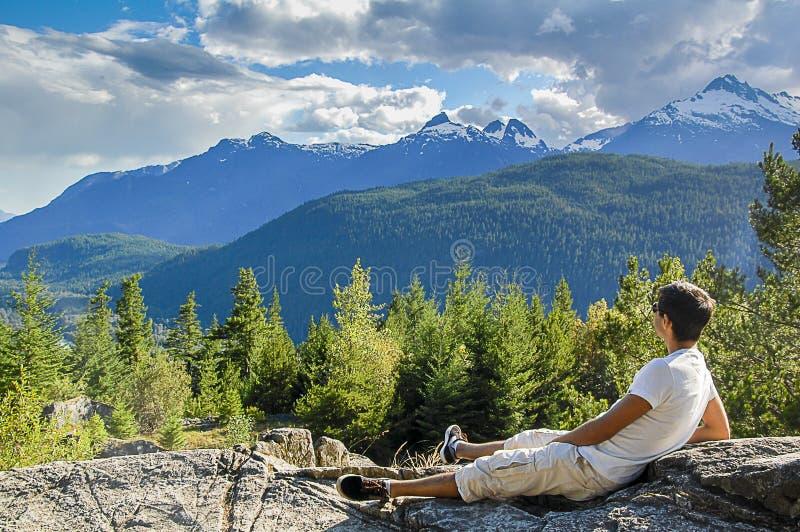 Jeune homme s'asseyant sur des roches regardant des montagnes photo stock