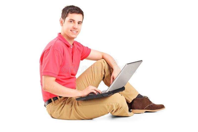 Jeune homme s'asseyant sur l'étage et travaillant sur un ordinateur portable photographie stock libre de droits