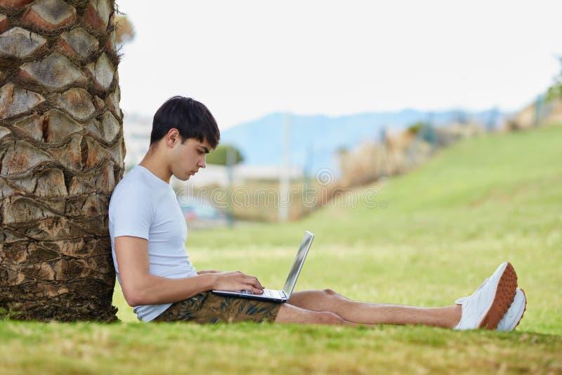 Jeune homme s'asseyant sur l'herbe utilisant l'ordinateur portable photos libres de droits