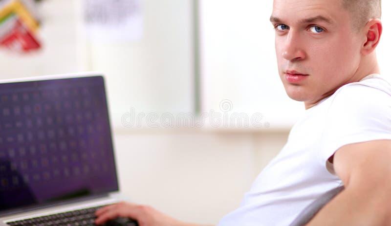 Jeune homme s'asseyant sur la chaise avec l'ordinateur portable photo stock
