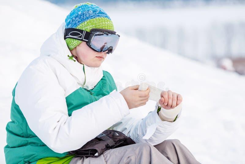 Jeune homme s'asseyant sur la neige avec le surf des neiges photographie stock libre de droits
