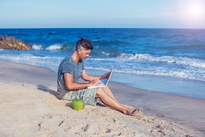 Jeune homme s'asseyant sur la plage avec l'ordinateur portatif image stock