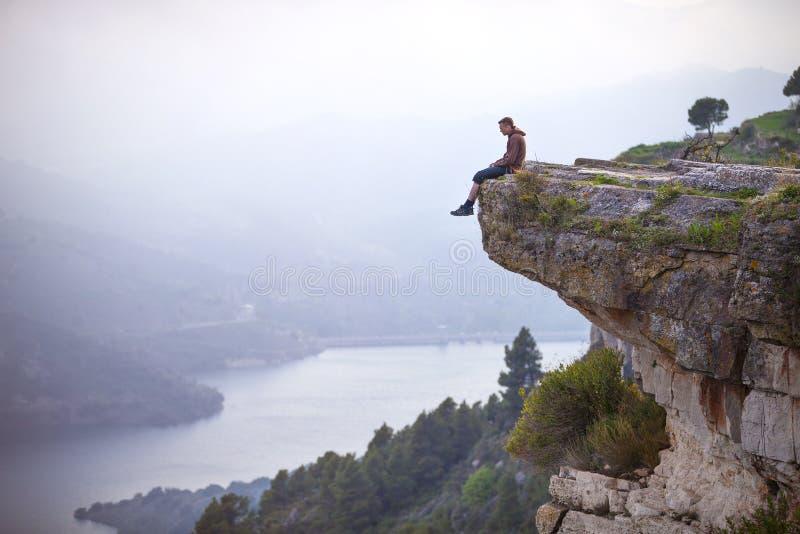 Jeune homme s'asseyant sur le bord de la falaise et regardant la rivière image stock