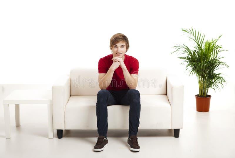 Jeune homme s'asseyant sur le divan photos libres de droits