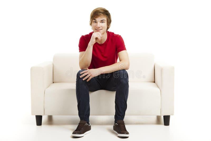 Jeune homme s'asseyant sur le divan image stock