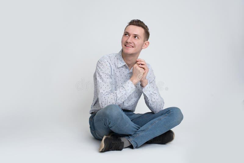 Jeune homme s'asseyant sur le plancher d'isolement photo stock