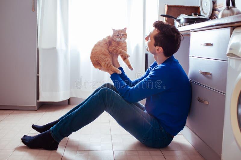 Jeune homme s'asseyant sur le plancher de la cuisine avec un chat image libre de droits