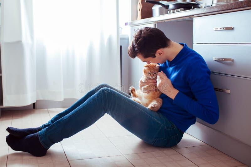 Jeune homme s'asseyant sur le plancher de la cuisine avec un chat images stock