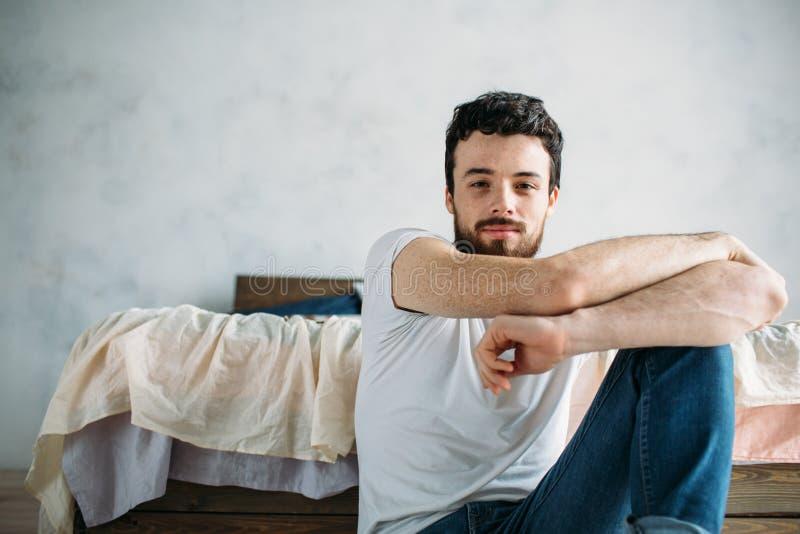 Jeune homme s'asseyant sur le plancher près du lit photographie stock