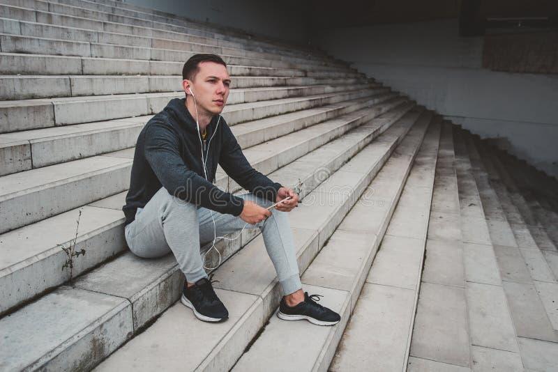 Jeune homme s'asseyant sur le pont moderne dans la ville, utilisant son smartphone photographie stock libre de droits