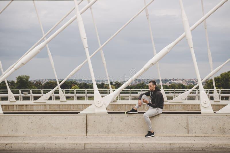 Jeune homme s'asseyant sur le pont moderne dans la ville, utilisant son smartphone image stock