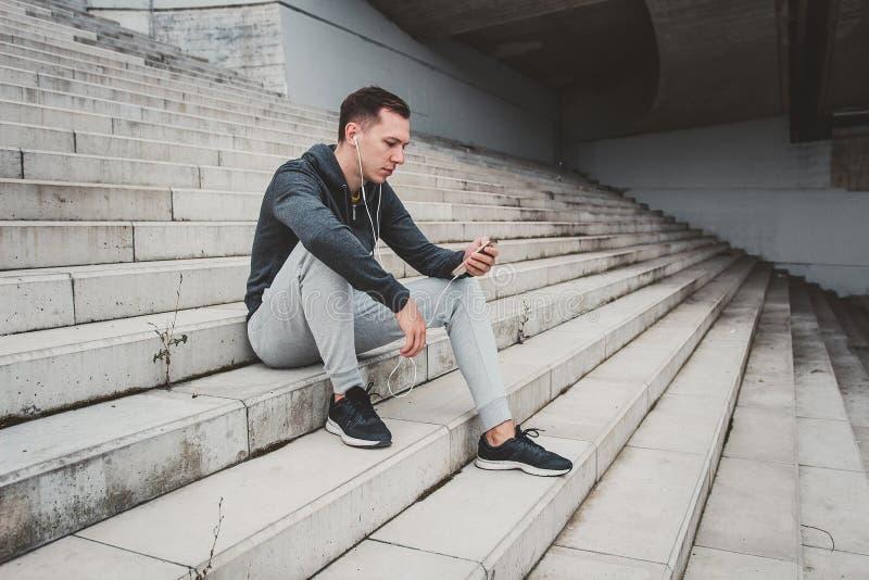 Jeune homme s'asseyant sur le pont moderne dans la ville, utilisant son smartphone photographie stock
